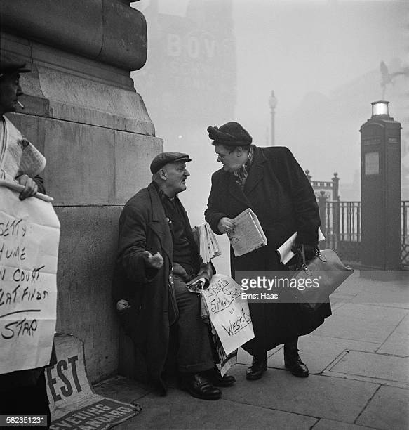 A woman talks to a newspaper seller outside Piccadilly Circus tube station London circa 1953