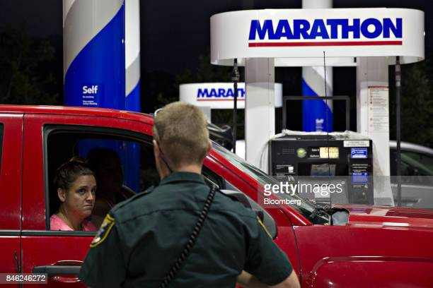 A woman talks to a police officer as he announces the closing of a Marathon gas station due to a county wide curfew in Estero Florida US on Tuesday...