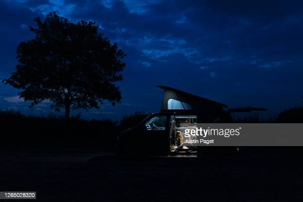 woman talks to her daughter in their campervan at night - freedom stock pictures, royalty-free photos & images