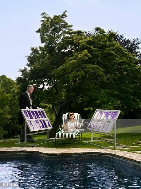 Woman tanning as butler adjust solar panel.