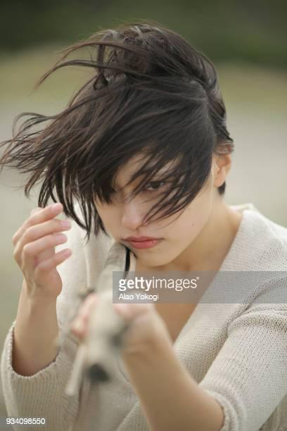 a woman targeting something on the beach - ショートヘア ストックフォトと画像