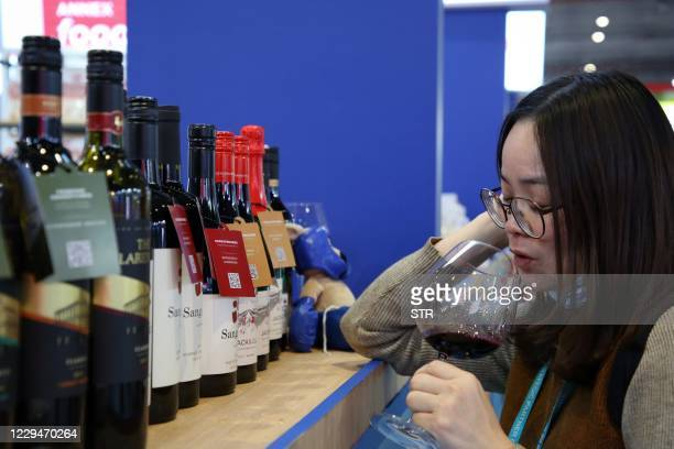 Woman tastes red wine from Australia at the Food and Agricultural Products exhibition at the third China International Import Expo in Shanghai on...