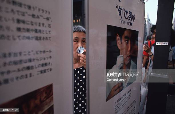 A woman tasting beer at a beer promotion on a main street in the shopping district in Ginza Tokyo