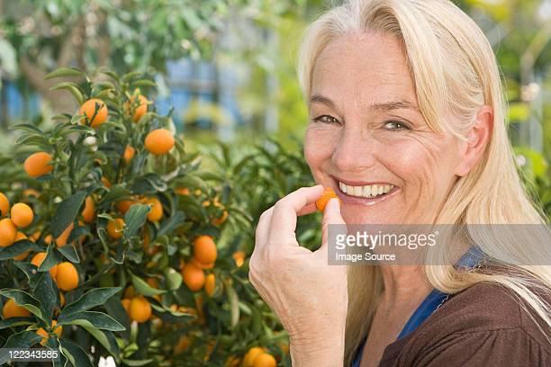 Woman tasting kumquat from tree