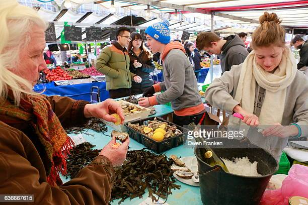 woman tasting oysters,Bastille Market, Paris