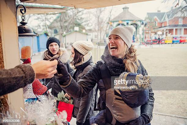 woman tasting product at an outdoors public market in winter. - quebec stock pictures, royalty-free photos & images