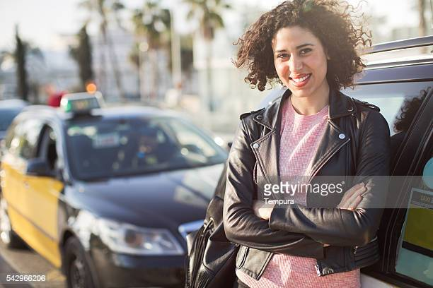 woman taxi driver next to her car. - taxi driver stock photos and pictures