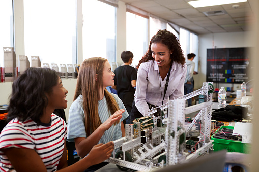 Woman Teacher With Female College Students Building Machine In Science Robotics Or Engineering Class 1133836360