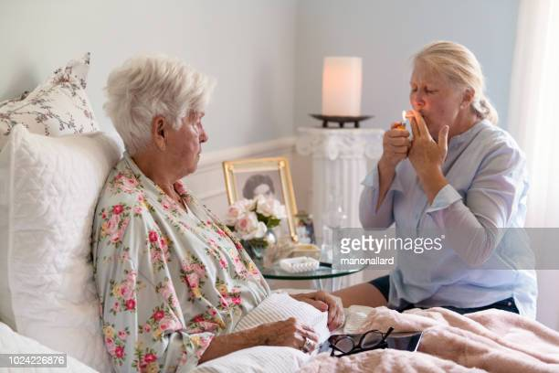 a woman teaches her mother how to smoke marijuana joint medicinal cannabis - hospice stock pictures, royalty-free photos & images