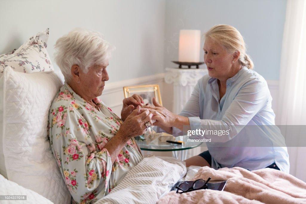 A woman teaches her mother how to smoke marijuana joint medicinal cannabis : Stock Photo