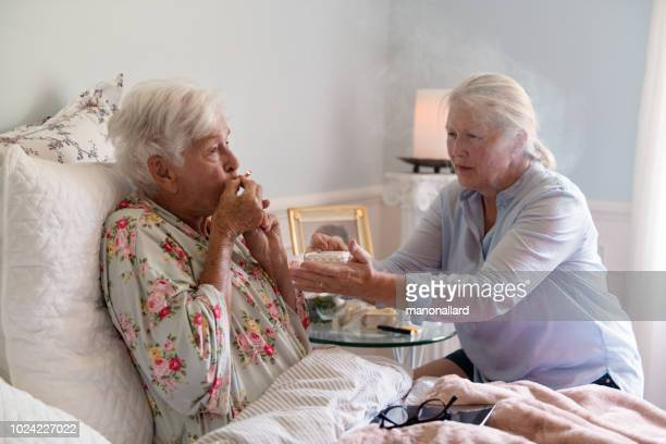 a woman teaches her mother how to smoke marijuana joint medicinal cannabis - medical cannabis stock photos and pictures
