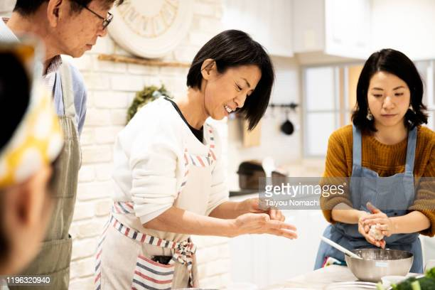 a woman teaching a parent and child cooking class - シンプルな暮らし ストックフォトと画像