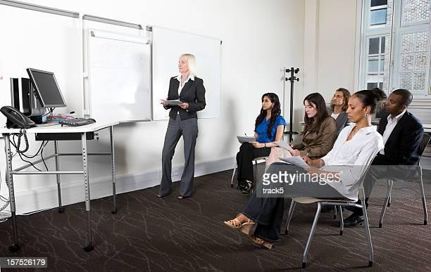Femme enseignement et écrit sur un tableau blanc de classe de l'éducation des adultes.