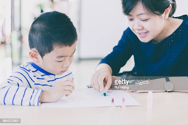 Woman teaching child to paint