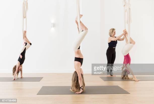 Woman teaching children aerial yoga