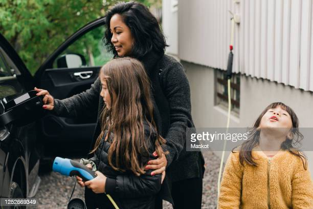 woman teaching daughter to charge electric car at charging station - electric car stock pictures, royalty-free photos & images