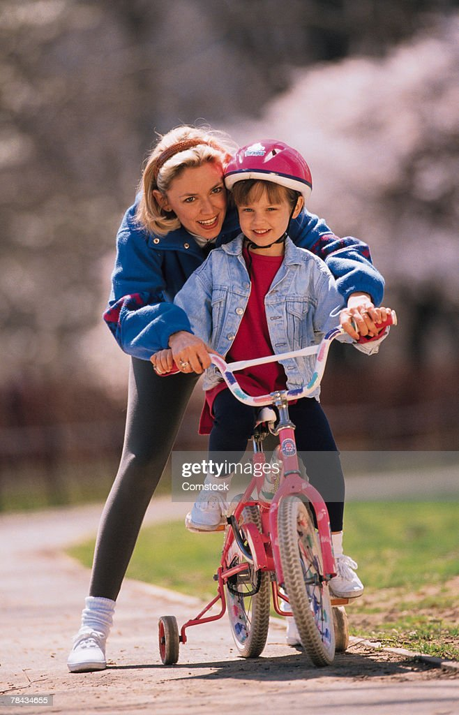 Woman teaching daughter to ride a bicycle : Stockfoto