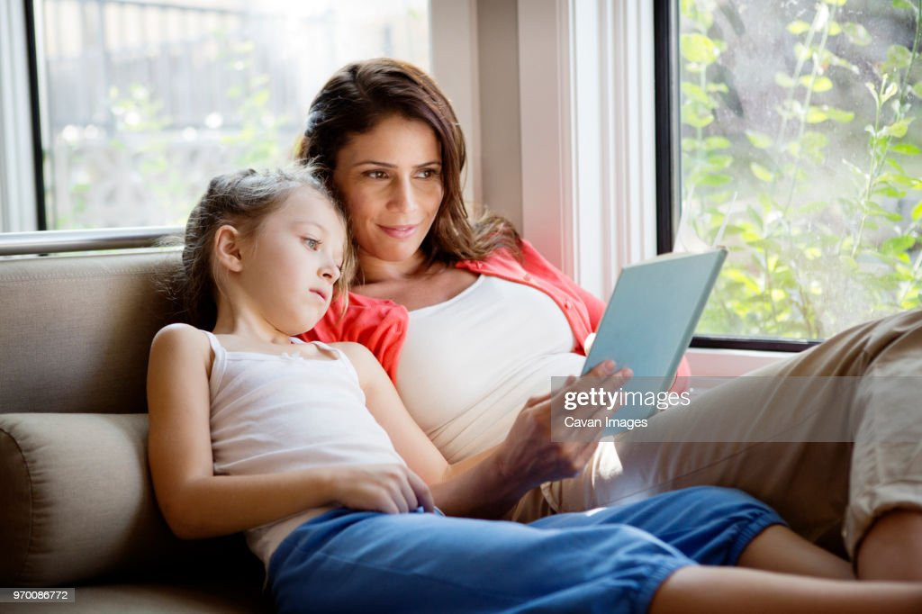 Woman teaching daughter while relaxing on sofa at home : Stock Photo