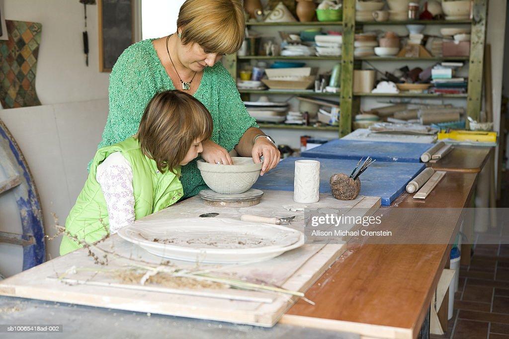 Woman teaching girl (4-5) how to do ceramics : Foto stock