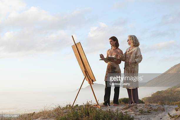 Woman teaching young man how to paint