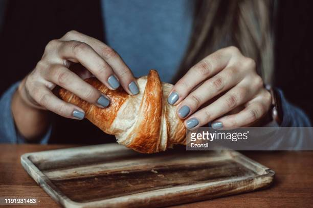 woman tearing sweet croissant - bun stock pictures, royalty-free photos & images
