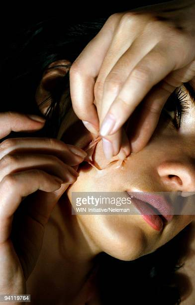 Woman tearing the skin of her face, Lugansk, Ukraine