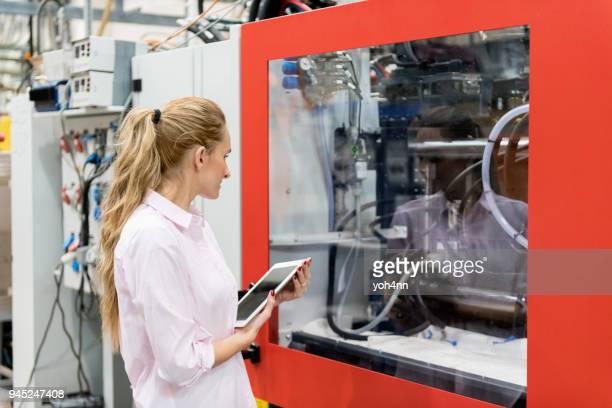 Technicien de la femme à l'aide de tablette & examinant machine cnc