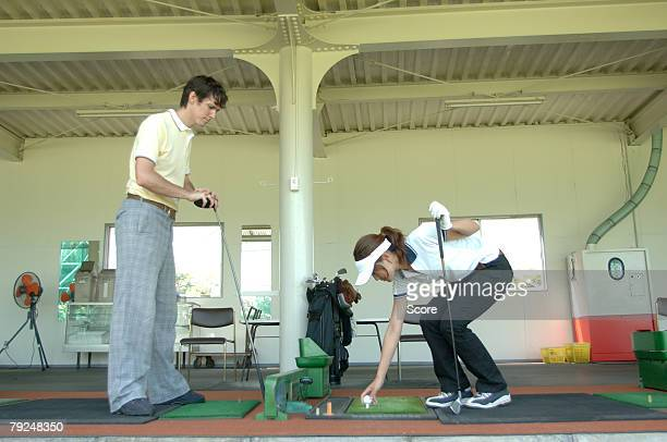 Woman teeing up whilst her partner looks on