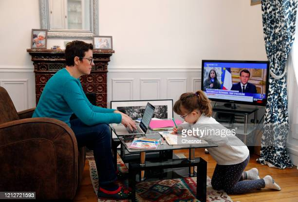 A woman telecommutes from her home with her daughter playing due to school closings due to the Coronavirus epidemic on March 16 2020 in Paris France...