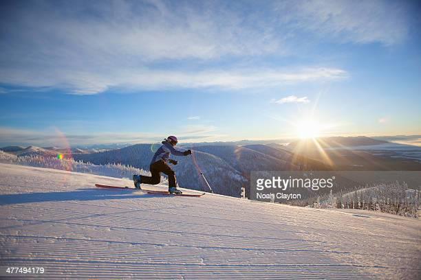 Woman telemark skiing on fresh groomed run