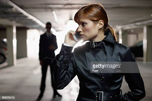 Woman Telephoning While Man Lurks in the Shadows
