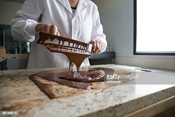 Woman tempering melted chocolate on a marble surface
