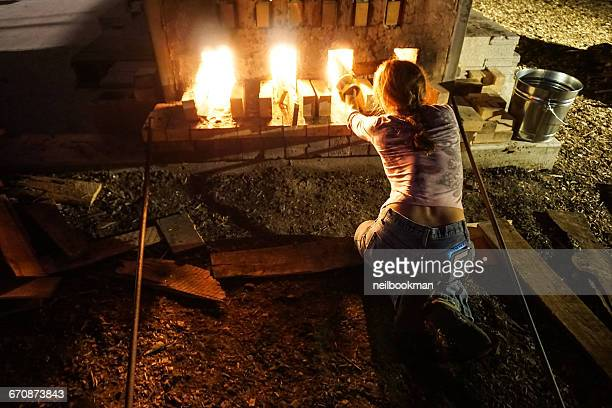 Woman tending to fire of wood kiln at night