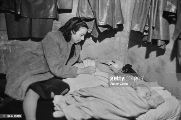 Woman tending to two babies in an air raid shelter during the Blitz, London, October 1940. Original Publication: Picture Post - 308 - Shelter Life -...