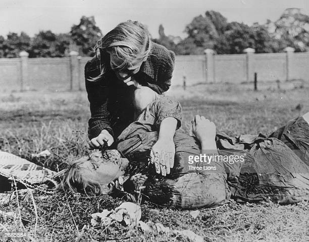A woman tends to a victim of Nazi atrocities in Poland during World War II