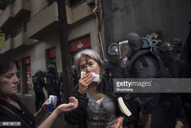 A woman tends to her injuries in front of riot police near a school being used as a polling station for the banned referendum in Barcelona Spain on...
