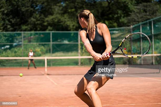 Woman tennis player about to hit a backhand
