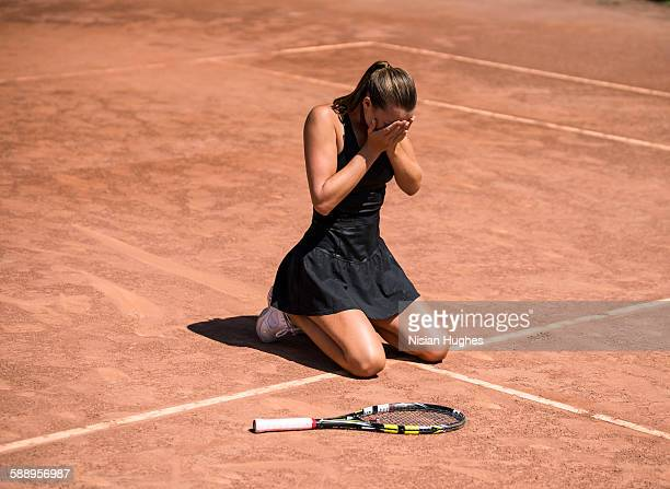 Woman tennis player on her knees, hands over face