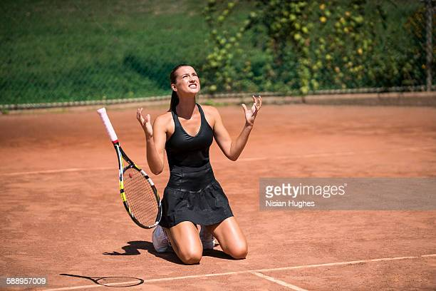 Woman tennis player on her knees with hands up