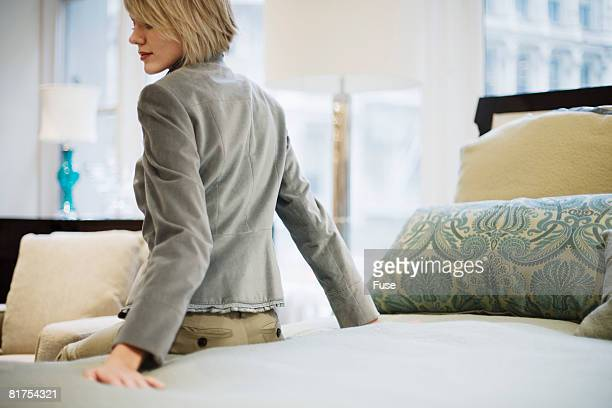 Woman Testing Bed in Furniture Store