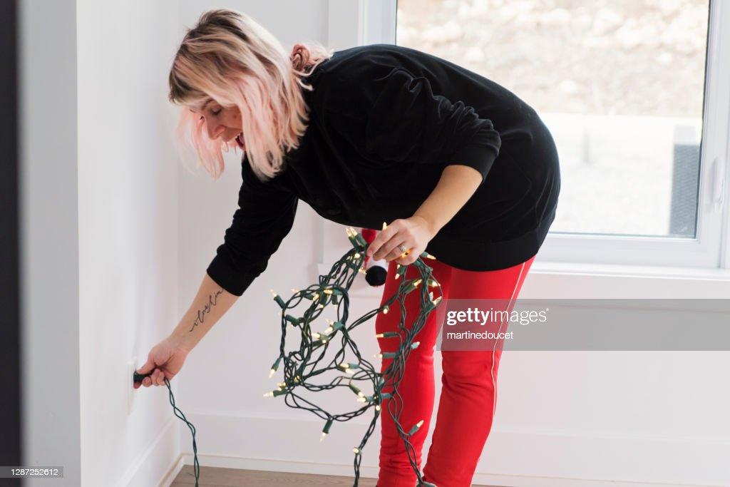 Woman testing Christmas lights. : Stock Photo