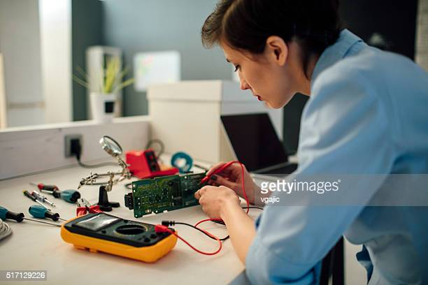 Woman Testing circuit board in her office.
