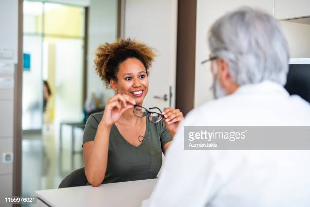 woman testing out her new eyeglasses in ophthalmology office - eyesight stock pictures, royalty-free photos & images