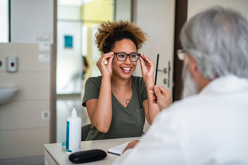 Woman testing out her new eyeglasses in ophthalmology office 1155980510