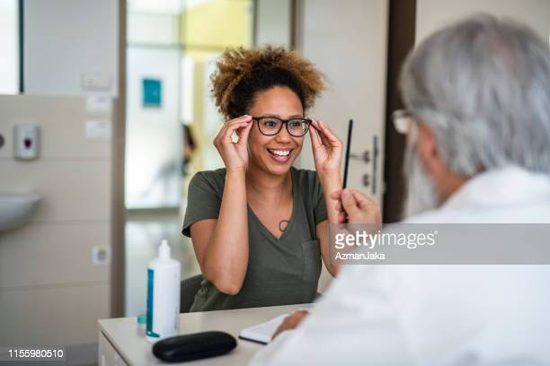 woman testing out her new eyeglasses in ophthalmology office - eye test equipment stock pictures, royalty-free photos & images