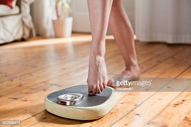 woman testing personal scales, partial view - mass unit of measurement stock pictures, royalty-free photos & images