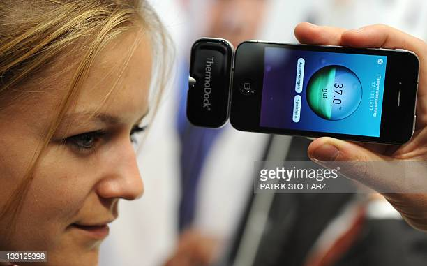 A woman tests an Iphone device for measuring body temperature at the Medica World Forum for Medicine fair on November 17 2011 in Duesseldorf western...
