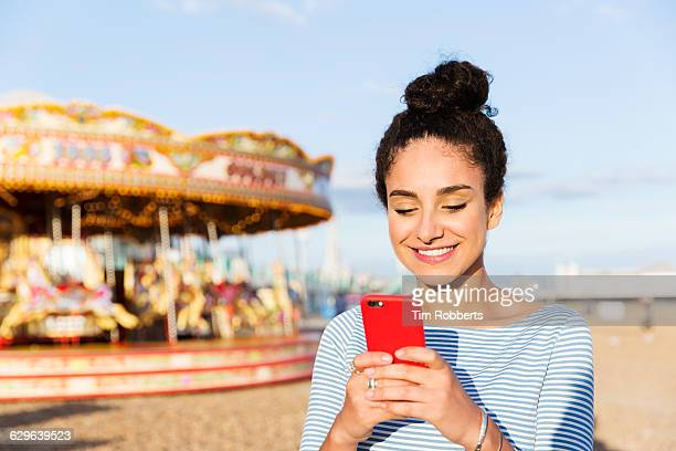 woman text messaging at beach fairground - topknot stock pictures, royalty-free photos & images