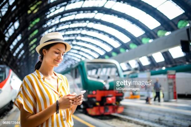 messaggi di testo della donna alla stazione ferroviaria. - treno foto e immagini stock