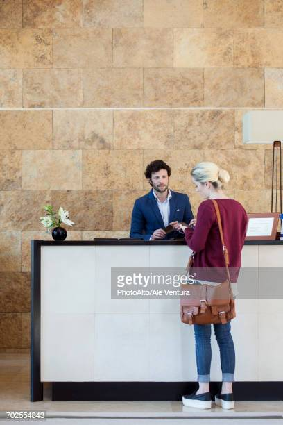 woman text messaging during transaction with receptionist - checkout stock pictures, royalty-free photos & images